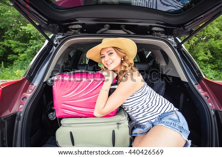 Young attractive woman sitting in the open trunk of a car. Summer road trip - stock photo