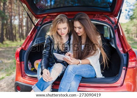 Young attractive woman sitting in the open trunk of a red car. Summer road trip - stock photo
