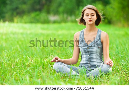 young, attractive woman sitting on green grass (meadow, glade) cross-legged in lotus position meditating - stock photo