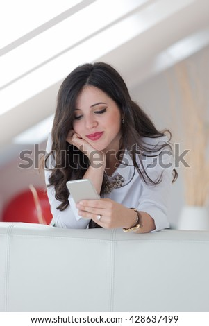 Young attractive woman sitting on sofa at home, talking on mobile phone - stock photo