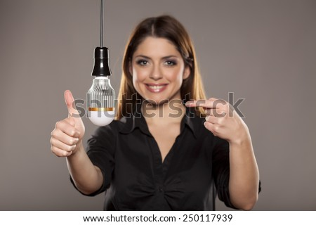 Young attractive woman smiling and comparing two types of light bulbs, saving light bulb and normal light bulb. Pointing towards the saving light bulb. studio portrait on white background. - stock photo