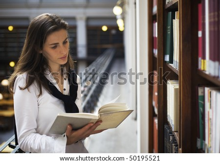 Young attractive woman standing at bookshelf in old university library reading a book. - stock photo