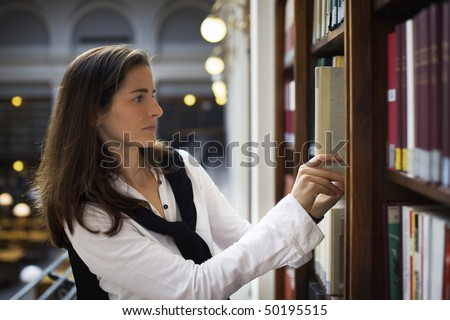 Young attractive woman standing at bookshelf in old university library searching for  books. - stock photo