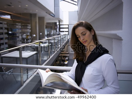 Young attractive woman standing at handrail in modern university library reading a book. - stock photo