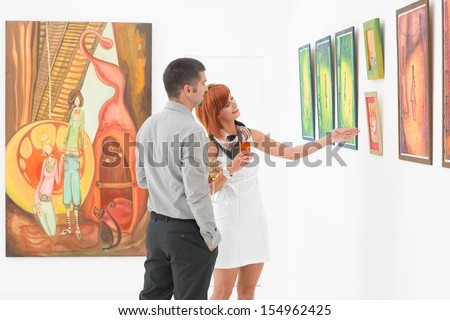 young attractive woman standing in an art gallery next to a man, pointing at some artwork displayed on wall