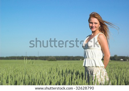 Young attractive woman standing in the green field