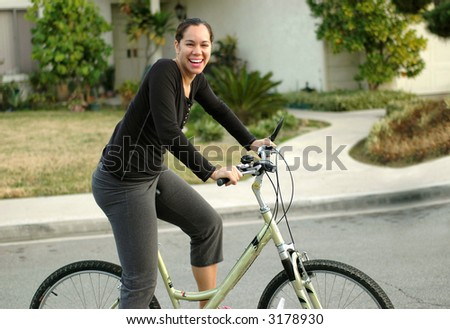 Young attractive woman staying in shape by riding a bike - stock photo