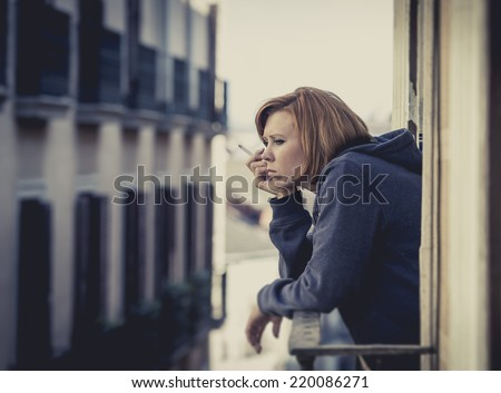 young attractive woman suffering depression and smoking in stress outdoors at home balcony terrace window in pain and grief feeling sad and desperate in urban background - stock photo