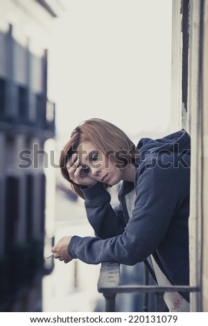 young attractive woman suffering depression and smoking in stress outdoors at home balcony terrace window in pain and grief feeling sad and desperate in urban background