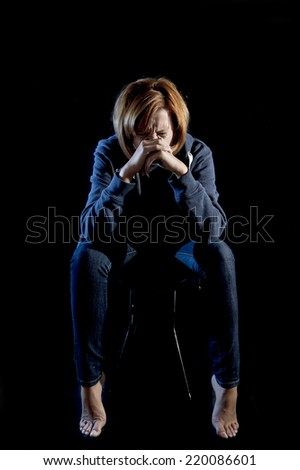 young attractive woman suffering depression crying in stress sitting alone in pain and grief feeling sad and desperate isolated on black background - stock photo