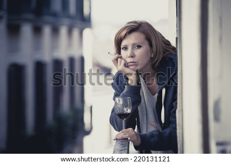 young attractive woman suffering depression smoking and drinking wine in stress outdoors at home balcony terrace window in pain and grief feeling sad and desperate in urban background - stock photo