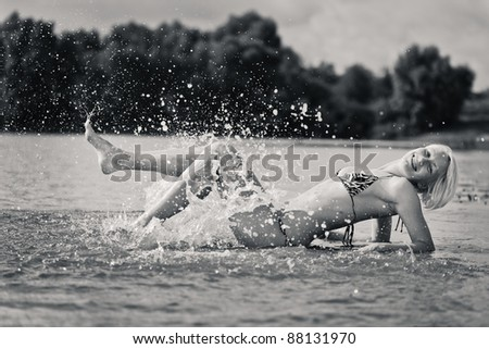 Young attractive woman sunbathing in the water - stock photo
