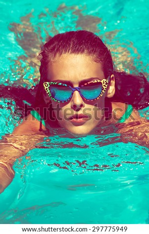 young attractive woman swimm in  pool with sunglasses   - stock photo