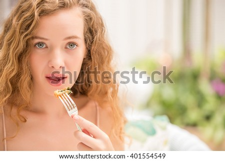 Young attractive woman taking a good time eating some natural healthy food.