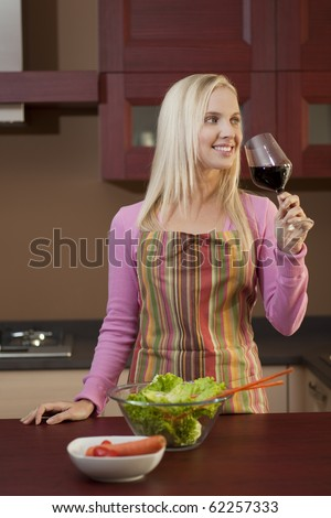 Young attractive woman tasting red wine before dinner