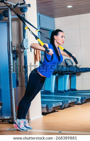 Young attractive woman training with htrx fitness straps in the gym's studio - stock photo