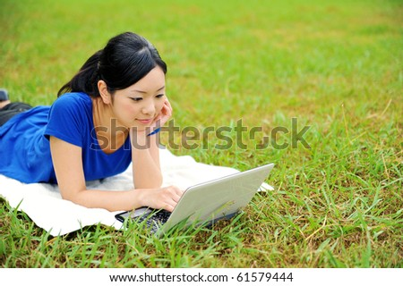 young attractive woman using laptop in the park - stock photo
