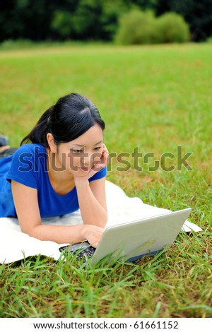 young attractive woman using laptop in the park