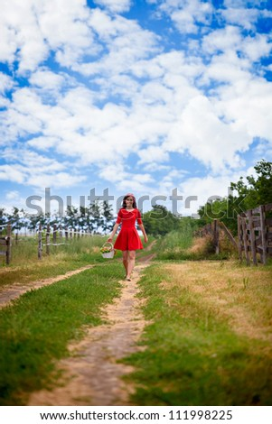 Young attractive woman walking in nature in red dress