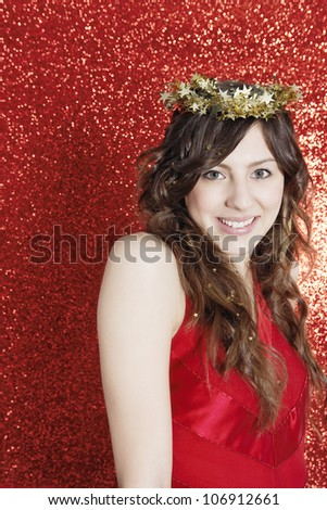 Young attractive woman wearing a gold tinsel tiara, smiling against a red glitter background.
