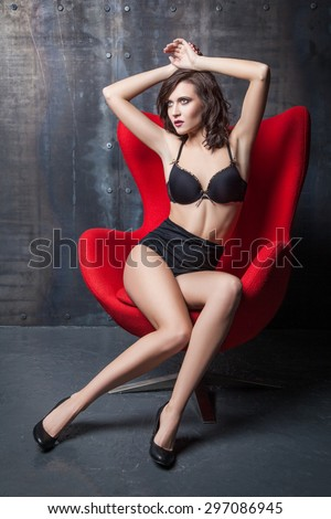young attractive woman wearing sexy black lingerie reclining provocatively on chair. industrial interior. looking at camera. studio shot. Developed from RAW. retouched with special care and attention.