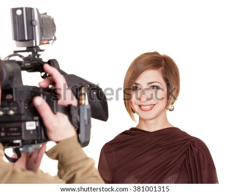 Young attractive woman with a beautiful smile gives an interview to the camcorder. Studio shot.Image isolated on white background. - stock photo