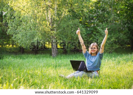 Young attractive woman with a laptop sitting on the grass. Happy face and smile.