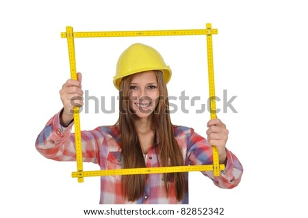 Young attractive woman with a yellow helmet looks through a measuring stick - stock photo