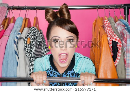Young attractive woman with clothes rack  - stock photo
