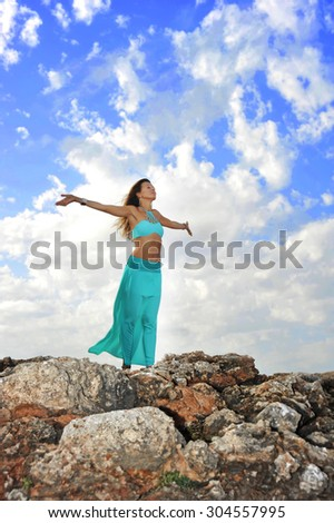 young attractive woman with cyan dress and opened arms in Zen yoga pose at rock mountain looking at horizon under blue sky with clouds in relax and spiritual serenity and freedom concept - stock photo