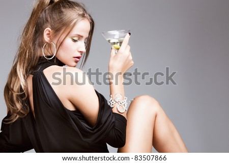 young attractive woman with glass of martini, profile, studio shot - stock photo