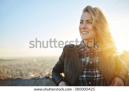 Young attractive woman with good mood enjoying beautiful city landscape while standing on a roof of building, charming smiling hipster girl relaxing after excursion during her amazing spring weekend  - stock photo
