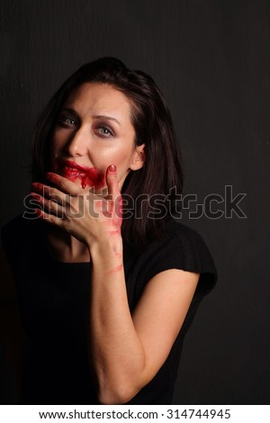 Young attractive woman with Halloween vampire makeup. low key image