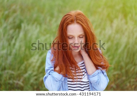 Young attractive woman with long red hair relaxing in a grassy field with her hands clasped behind her neck and eyes closed - stock photo