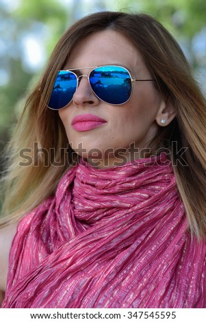 young attractive woman with natural big pink lips and blue sunglasses outside outdoor  - stock photo