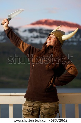 young attractive woman with nordic helmet posing with knife - stock photo