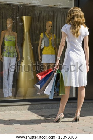 Young attractive woman with paper bags looking at a shop window with mannequins - stock photo