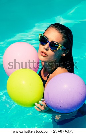 young attractive woman with sunglasses and balloons in the  pool
