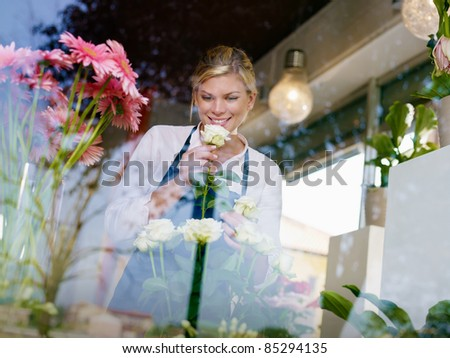 Young attractive woman working in flower shop, preparing bouquet and smelling white roses - stock photo