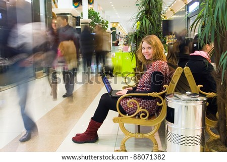 Young attractive woman working on laptop in the mall and using wireless technology. Motion blurred crowd (people) - stock photo