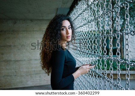 young attractive woman writing a message on her smart-phone against a background of contemporary modern building of concrete - stock photo