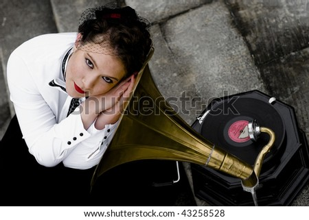 Young attractive women dressed in forties style listening to gramophone. - stock photo