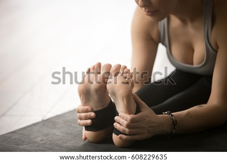 Young attractive yogi woman practicing yoga concept, sitting in paschimottanasana exercise, Seated forward bend pose, working out, wearing sportswear, wooden floor studio background, focus on legs