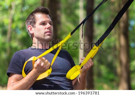Young attractiveman does suspension training with fitness straps outdoors in the nature. - stock photo