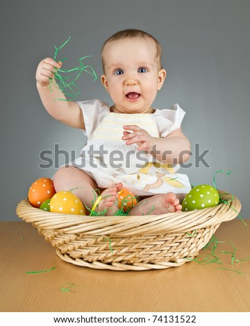 Young babay girl sitting and playing with easter egg. Very cute baby. - stock photo