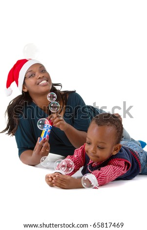 Young baby boy getting ready for christmas with his mother - stock photo