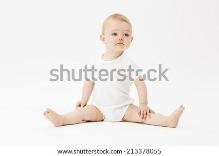 Young baby boy looking away, studio  - stock photo