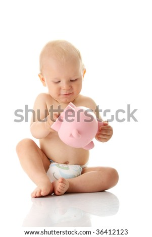 Young baby boy playing with pink piggy bank isolated - stock photo