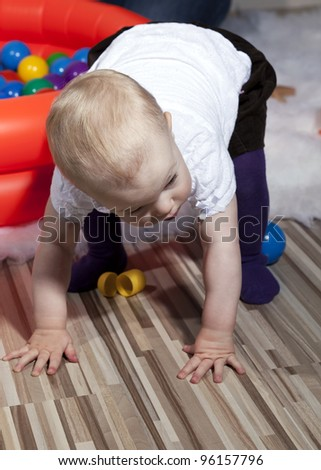 Young baby girl balanced on her fingertips about to take her first steps - stock photo