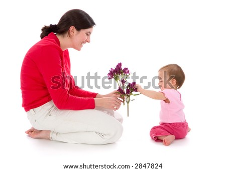 Young baby girl reaches out for a bouquet of purple flowers her mother is giving to her. Isolated on white background. - stock photo